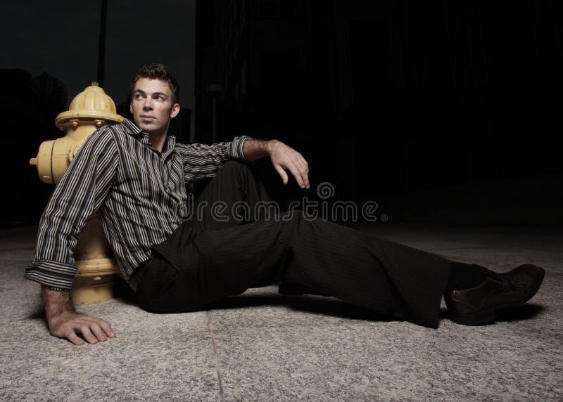 Mann, der durch einen Feuerhydranten sitzt lizenzfreies stockbild