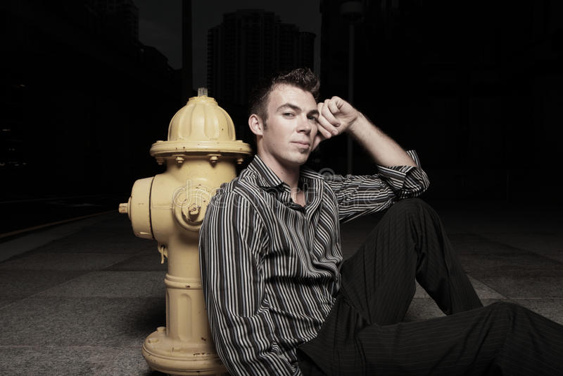Mann, der durch einen Feuerhydranten sitzt stockbilder