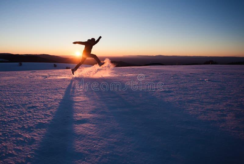Mann, der durch Schnee in der Winterlandschaft läuft stockbilder