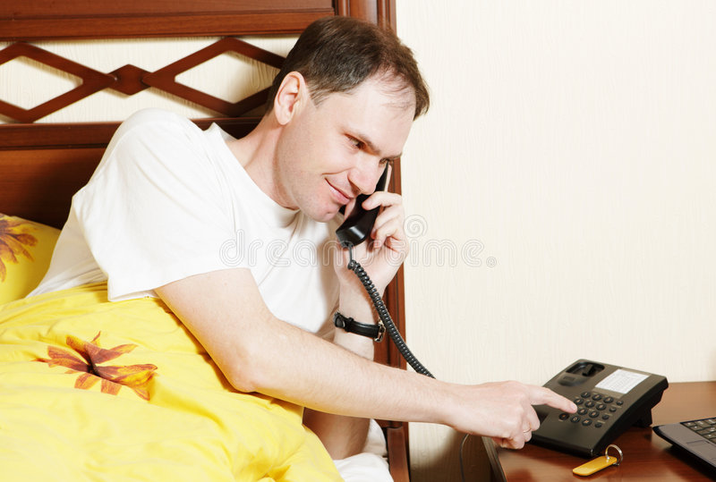 Mann, der durch Telefon benennt stockbild