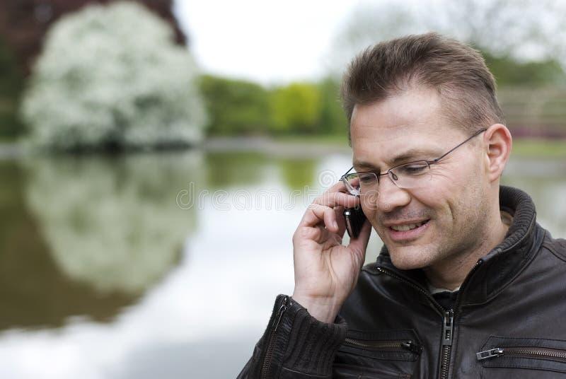 Mann, der durch Telefon spricht lizenzfreie stockbilder