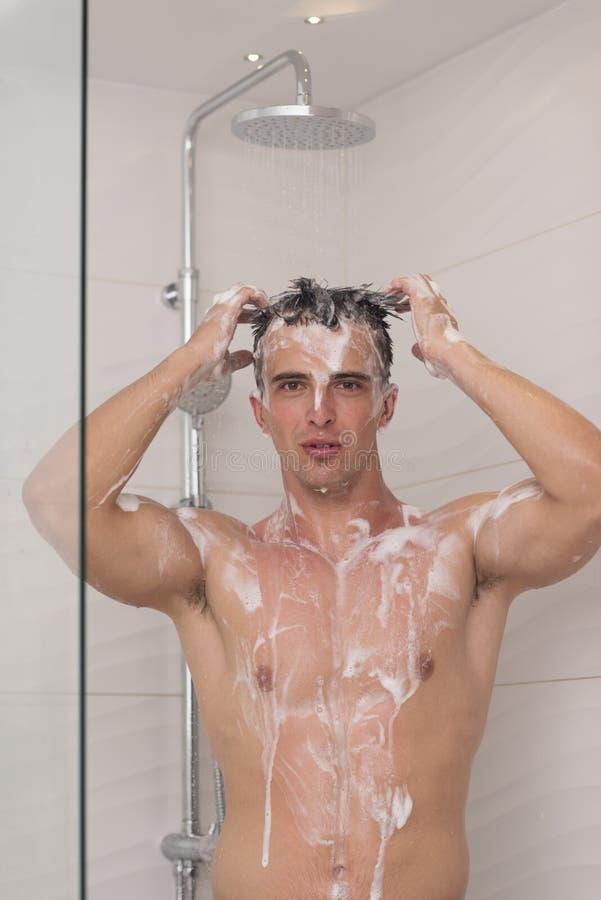 Mann, der Dusche im Bad nimmt stockbilder