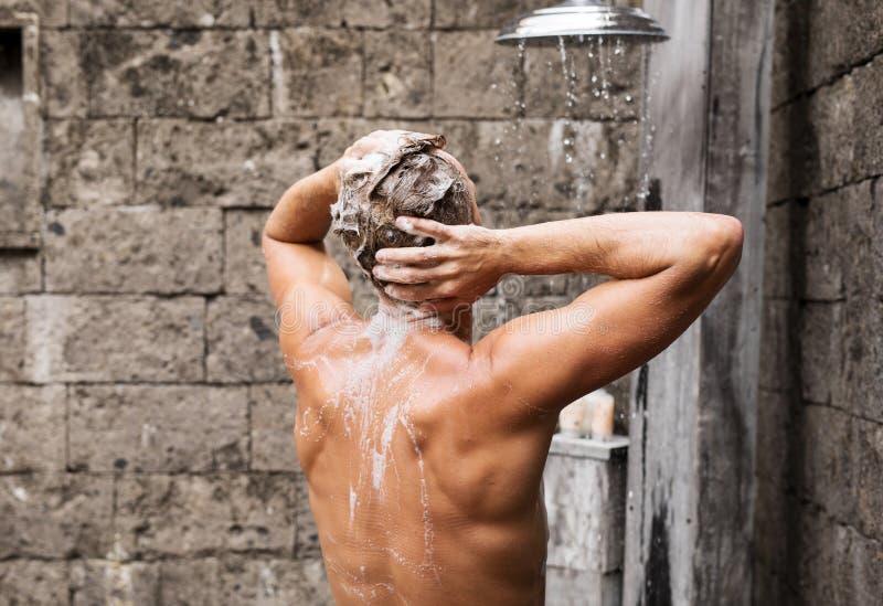 Mann, der Dusche nimmt und Haar wäscht lizenzfreie stockfotos