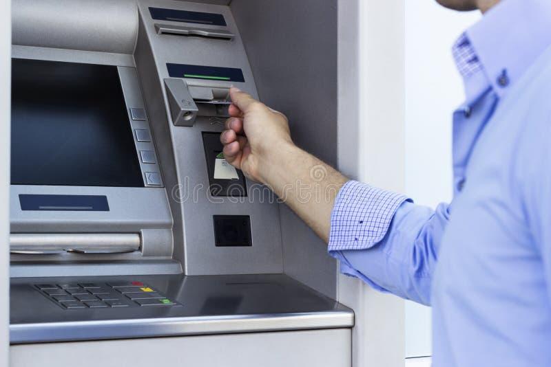 Mann, der ein ATM verwendet lizenzfreie stockfotos