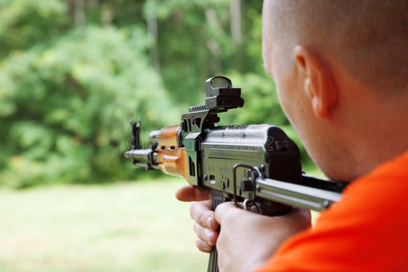 Mann, der ein automatisches Gewehr schießt stockfotografie