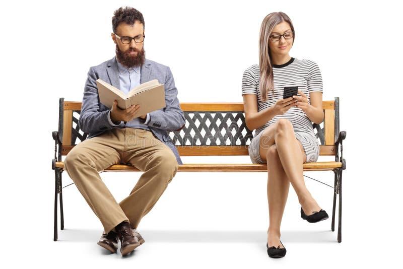 Mann, der ein Buch liest und eine Frau auf einer Bank sitzt und auf einem Mobiltelefon tippt lizenzfreie stockfotografie