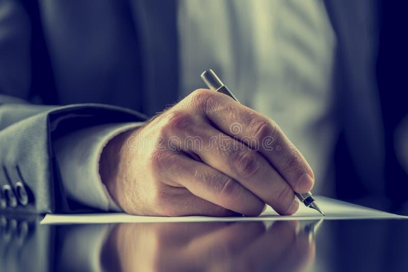 Mann, der ein Dokument unterzeichnet oder Korrespondenz schreibt lizenzfreies stockbild