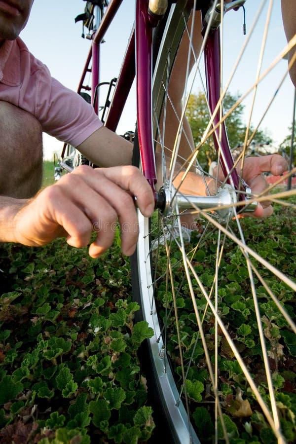 Mann, der ein Fahrrad - Vertikale repariert lizenzfreie stockfotos