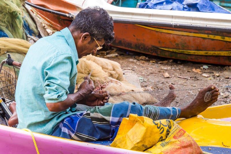 Mann, der ein Fischernetz repariert stockbild