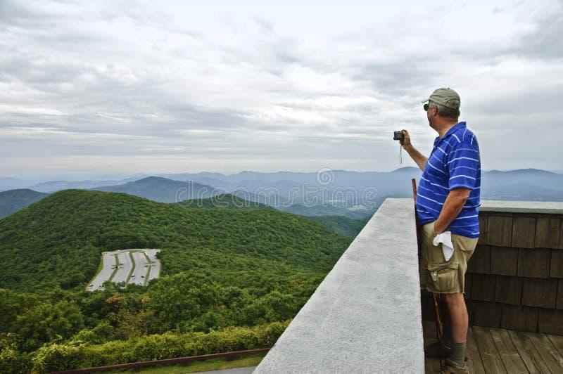 Mann, der ein Foto der Berge macht stockbilder