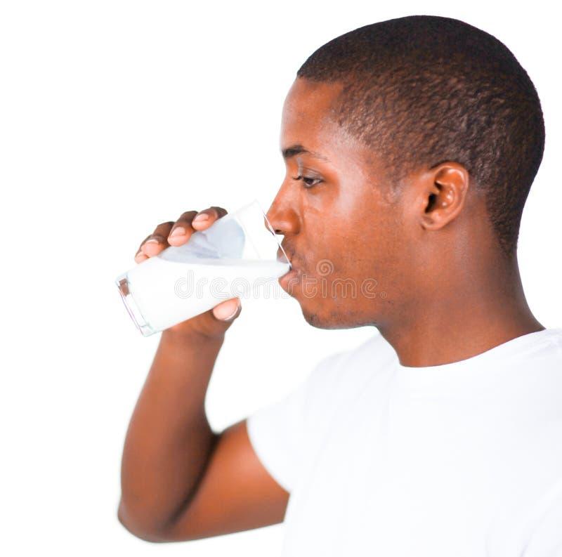 Mann, der ein Glas Milch trinkt stockbild