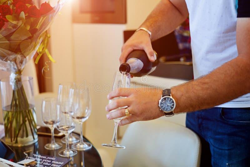 Mann, der ein Glas von Champagne gießt stockbilder