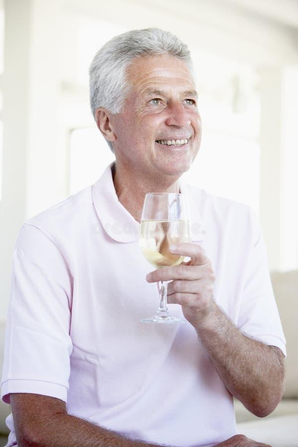 Mann, der ein Glas weißen Wein genießt stockbild