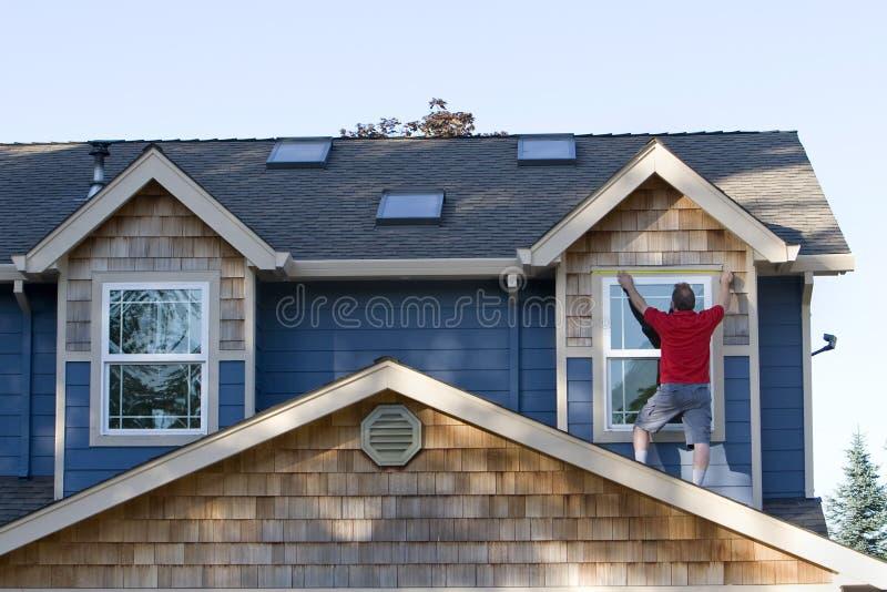 Mann, der ein Haus-Fenster - horizontal misst lizenzfreies stockbild