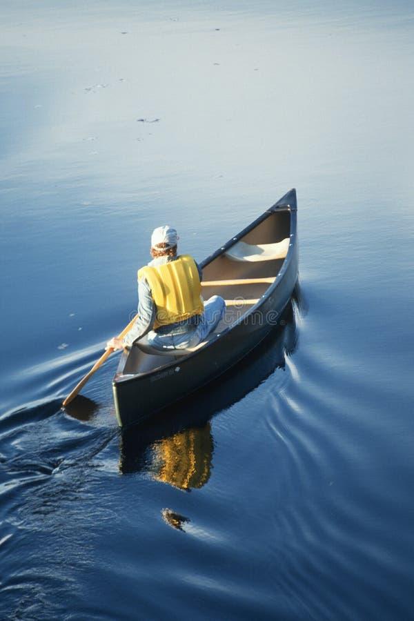 Mann, der ein Kanu rudert lizenzfreie stockfotos
