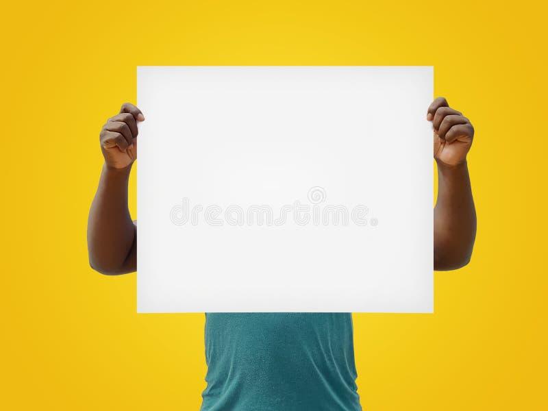 Mann, der ein leeres Weißzeichen über seinem Gesicht, lokalisiert auf einem gelben Hintergrund hält lizenzfreie stockfotos