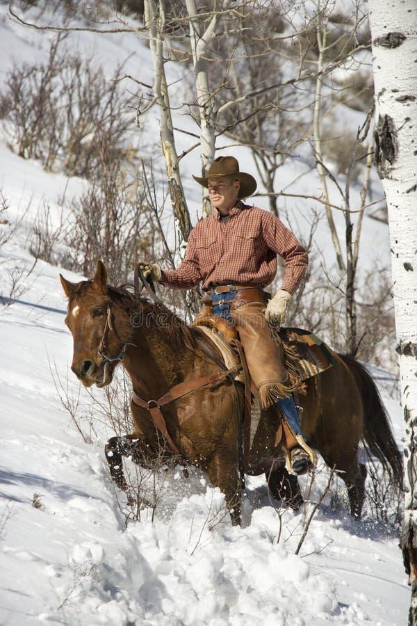 Mann, der ein Pferd der Schnee reitet lizenzfreie stockfotos
