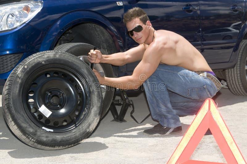 Mann, der ein Rad ändert stockfoto
