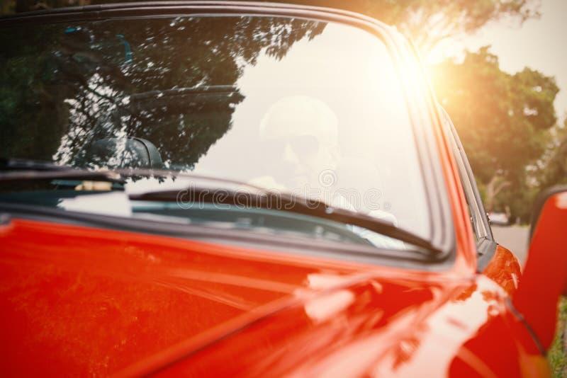 Mann, der ein rotes Auto fährt lizenzfreie stockfotografie