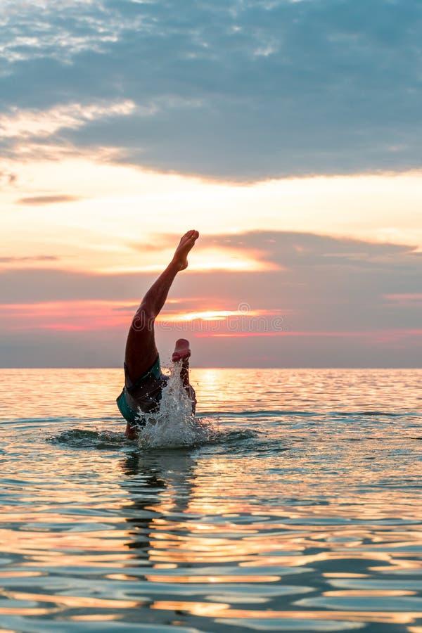 Mann, der ein Tauchen in den Strand macht stockfotografie