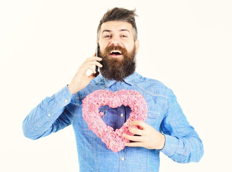 Mann, der ein Telefon lokalisiert auf weißem Hintergrund hält lizenzfreie stockfotografie