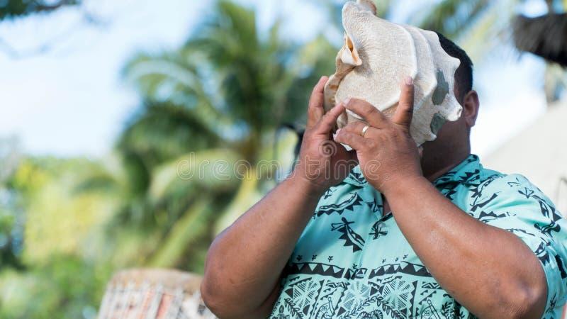 Mann, der ein Tritonshorn durchbrennt lizenzfreies stockbild