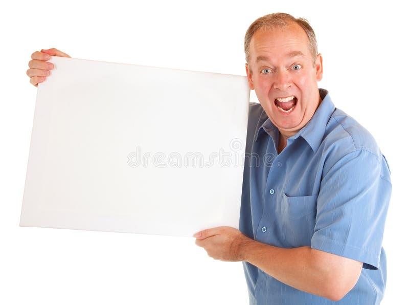 Mann, der ein unbelegtes weißes Zeichen anhält stockfotografie