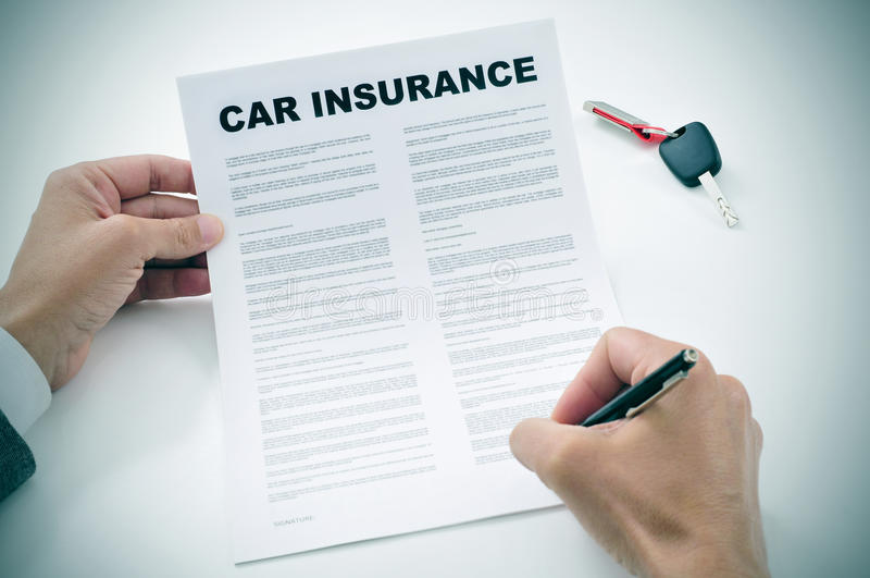Mann, der eine AutoVersicherungspolice unterzeichnet stockfotos