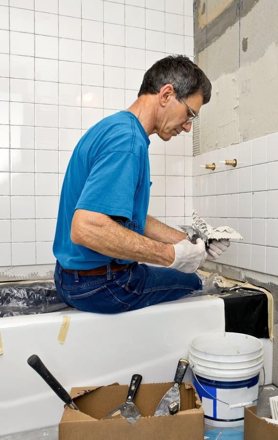 Mann, der eine Badezimmer-Wand mit Ziegeln deckt lizenzfreie stockfotografie