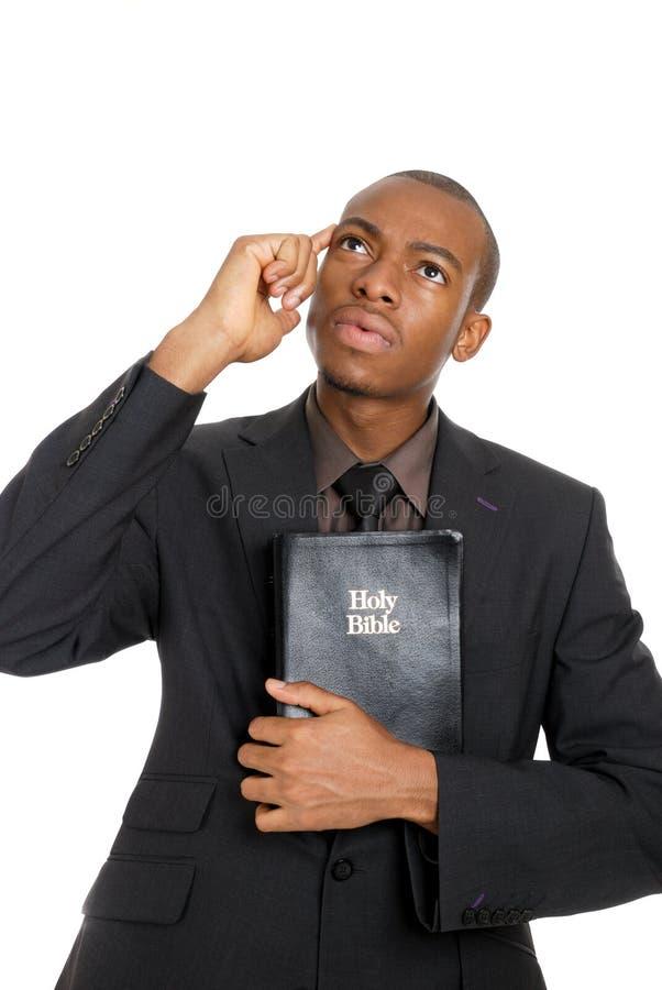 Mann, der eine Bibel anhält, während denkend stockfotografie