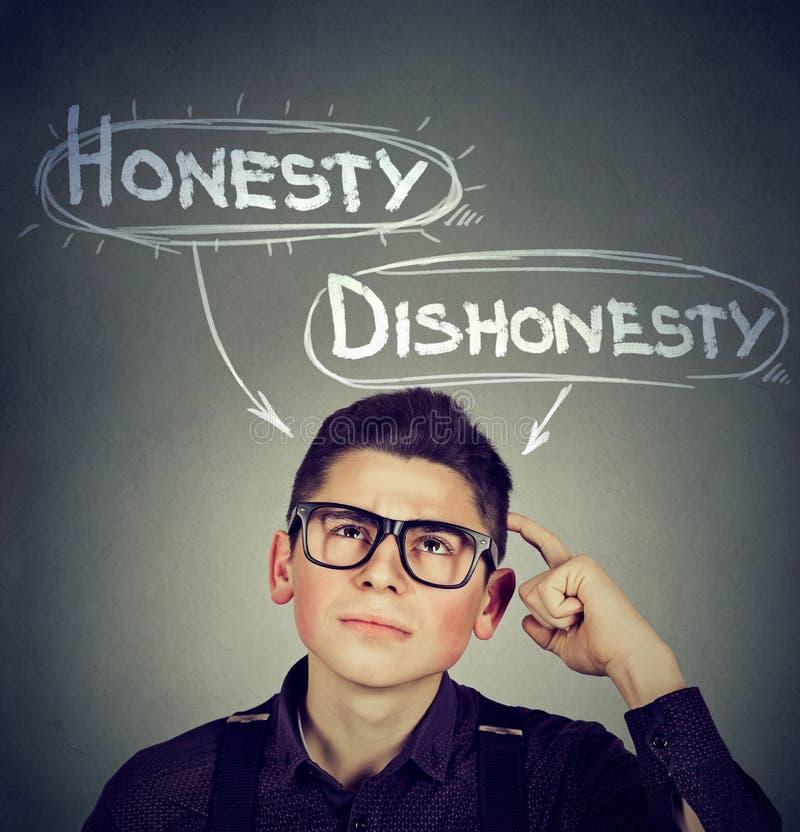 Mann, der eine Entscheidungsehrlichkeit gegen Unehrlichkeit macht stockbilder