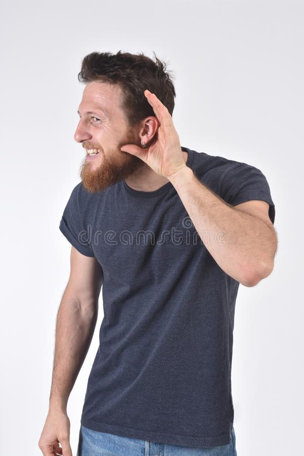 Mann, der eine Hand auf ihr Ohr setzt, weil sie nicht auf wei?em Hintergrund h?ren kann stockbild