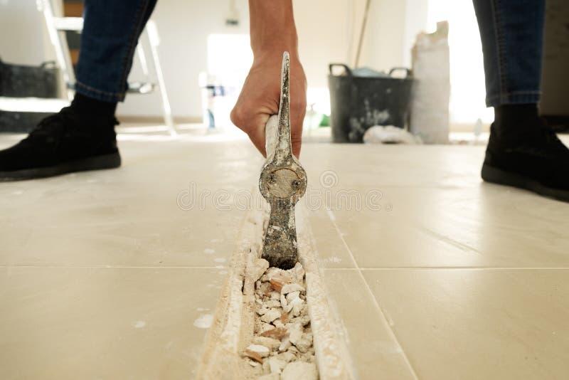 Mann, der eine Nut in einem Fliesenboden macht lizenzfreies stockbild
