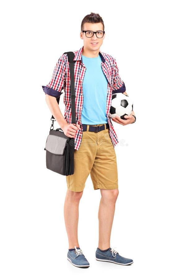 Mann, der eine Tasche und einen Fußball trägt stockfotografie
