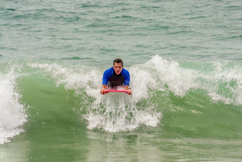 Mann, der eine Welle auf ein Boogie-Brett reitet lizenzfreies stockfoto