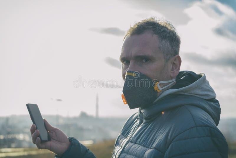 Mann, der eine wirkliche AntismogGesichtsmaske trägt und gegenwärtige Luftverschmutzung mit intelligentem Telefon App überprüft lizenzfreies stockfoto