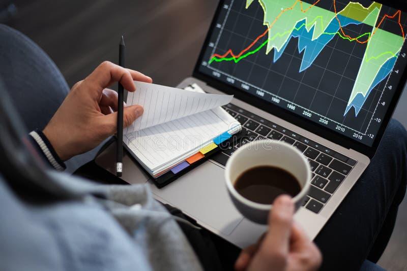 Mann, der an einem Projekt auf Laptop mit einem Tasse Kaffee arbeitet lizenzfreies stockbild