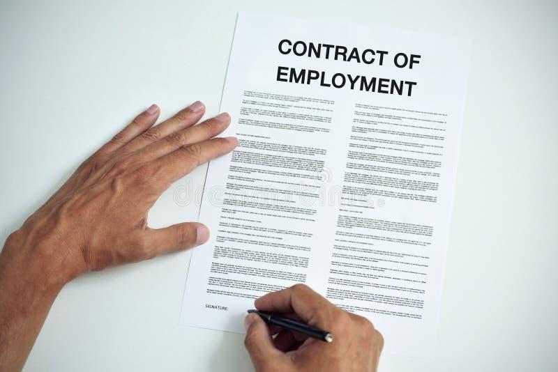 Mann, der einen Anstellungsvertrag unterzeichnet stockfotografie