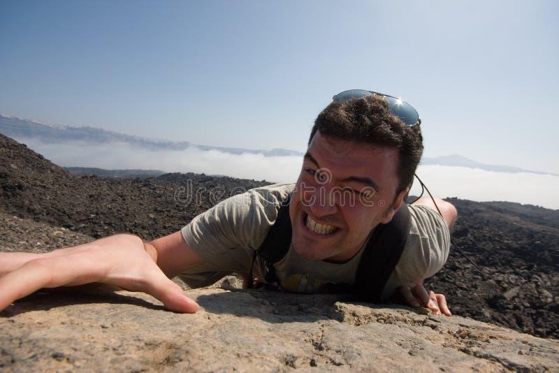 Mann, der einen Berg steigt stockfoto