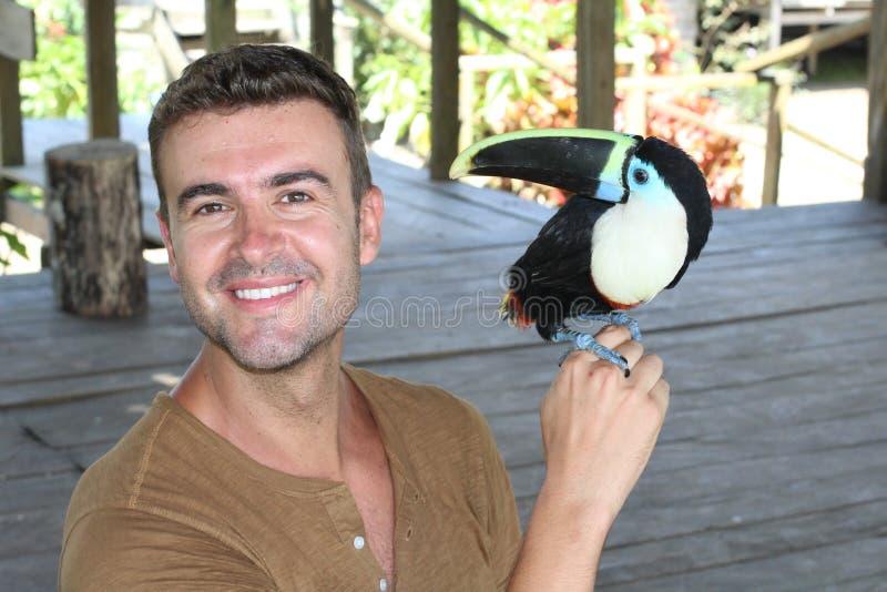 Mann, der einen bunten Tukanvogel hält lizenzfreies stockfoto