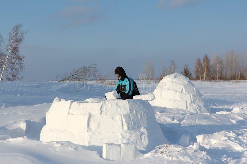 Mann, der einen Iglu von Schneeblöcken im Winter errichtet stockfotos