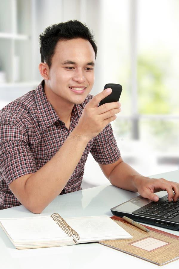 Mann, der einen Laptop verwendet und auf Handy texting stockfotos