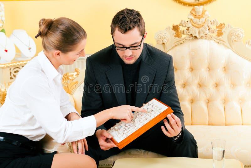 Mann, der einen Ring am Juwelier wählt stockfoto