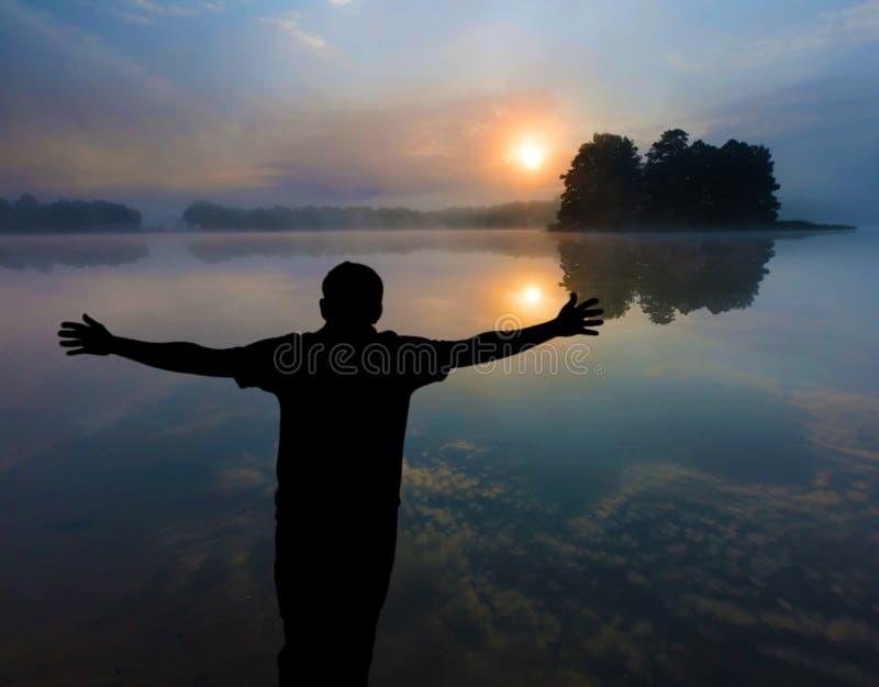Mann, der einen Sonnenaufgang über See aufpasst menschliches Schattenbild stockfotos
