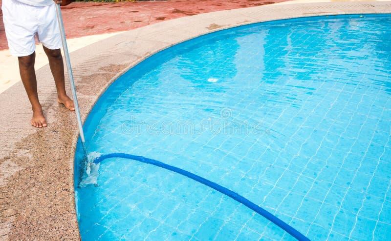Mann, der einen Swimmingpool im Sommer s?ubert Reiniger des Swimmingpools stockbilder