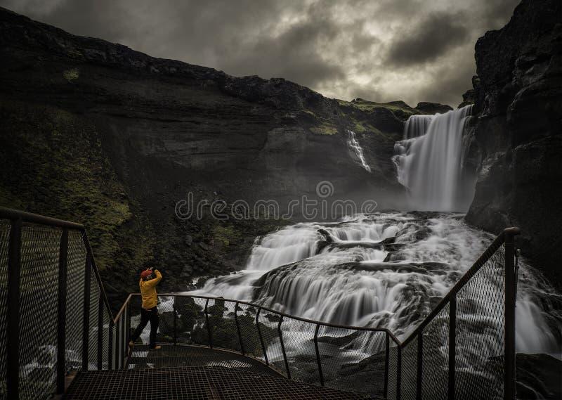 Mann, der einen Wasserfall betrachtet stockfotografie