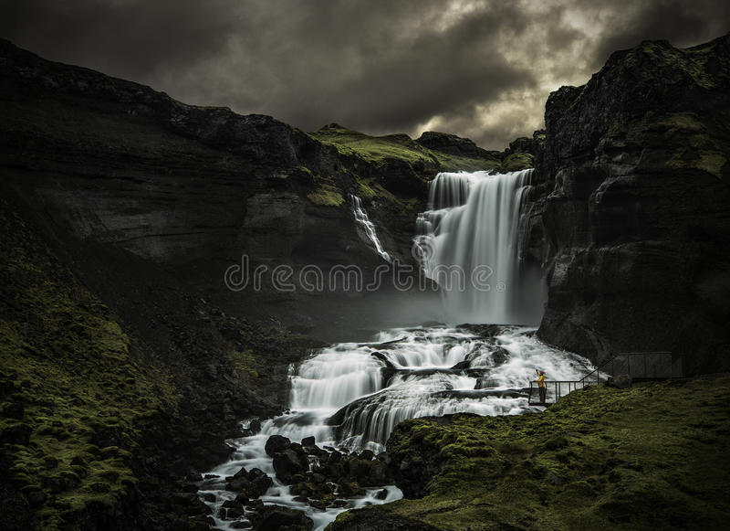 Mann, der einen Wasserfall betrachtet lizenzfreie stockfotografie
