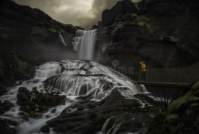 Mann, der einen Wasserfall betrachtet lizenzfreies stockfoto