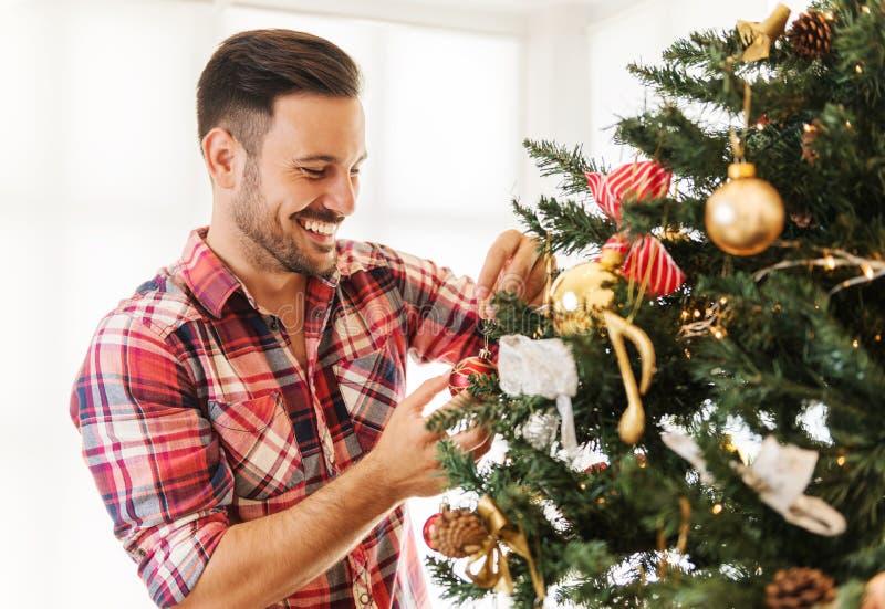 Mann, der einen Weihnachtsbaum verziert lizenzfreie stockfotos