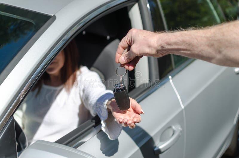 Mann, der einer Frau Autoschlüssel gibt lizenzfreie stockbilder